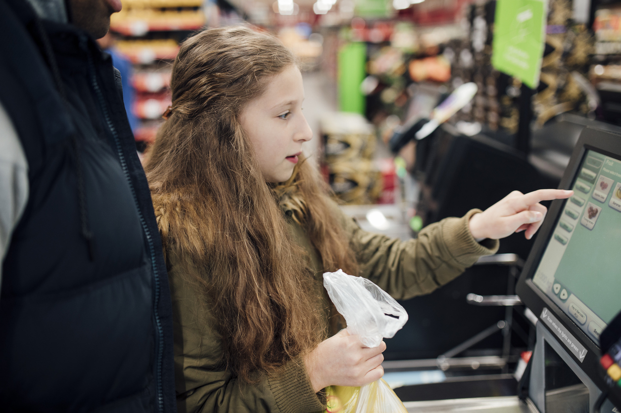 Little girl is at the self service checkout of the supermarket with her father. (iStock)